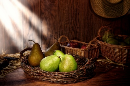 Green pears in an old wicker basket and natural organic fruits on a traditional country farm produce stand wood table in a vintage rural barn lit by diffused sunlight photo