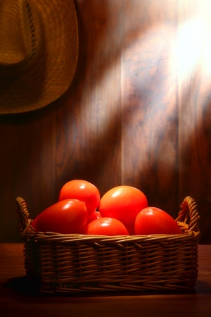 diffused: Organic plum tomatoes in an old wicker basket on a traditional country farm produce stand wood table in a vintage rural barn lit by soft diffused sunlight