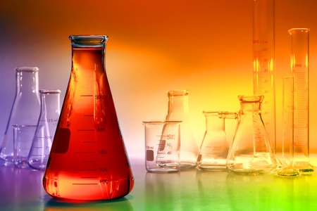 Scientific laboratory glass conical Erlenmeyer flask filled with orange amber chemical liquid with assorted empty scientific glassware for a chemistry experiment in a science research lab