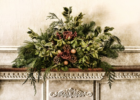fireplace: Grunge vintage Victorian Christmas floral arrangement decoration with roses within pine branches and cones with green foliage on antique fireplace mantel wood shelf in an old historic home in aged postcard style nostalgic muted colors Stock Photo