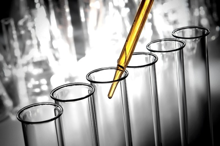 Laboratory pipette with emerging drop of yellow liquid over glass test tubes filled with chemical solution for a scientific experiment in a science research lab Stock Photo