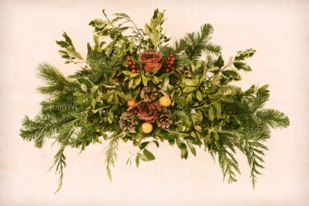 Grunge vintage Victorian Christmas floral arrangement decoration with roses within pine branches and cones with green foliage on antique paper background in aged postcard style nostalgic painterly muted colors