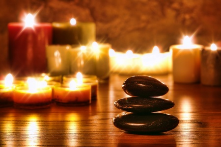 zen rocks: Symbolic Zen black polished smooth stones cairn stack and candles soft glowing in a spiritual religious temple for a meditation and reflection journey Stock Photo