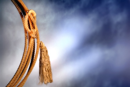 hondo: American West authentic rodeo cowboy lariat lasso hondo or honda noose with end loop rawhide speed burner detail and tassel over dramatic stormy sky  Stock Photo