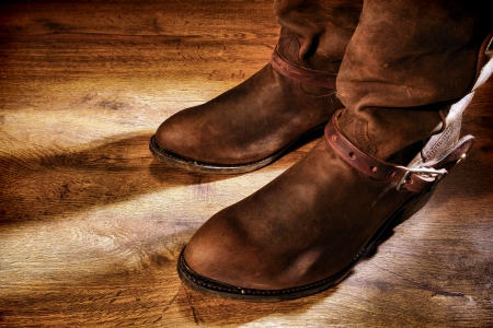 American West rodeo cowboy traditional working ranching boots with old leather Western riding spur straps on distressed grunge wood floor   photo