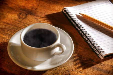 Cup of steamy hot black coffee with light steam and pencil on a spiral bound notebook open to a blank empty page for taking journal notes on a wood table in warm morning sunlight photo