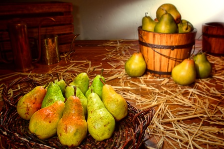Green Bartlett pears in a rustic wicker basket on an old wood table in a vintage rural barn with traditional growing and gardening objects at a country farm  photo