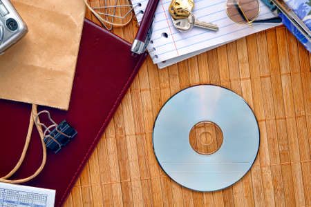 spread around: CD or DVD disc with empty blank copy space ready for text insert on a messy desk with everyday household stuff and things spread around