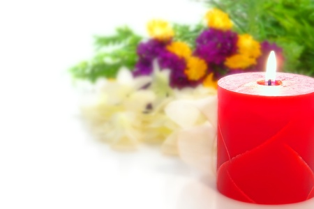 Red marble decorative pillar candle burning with a soft glowing flame in front of a blurry colorful flower bouquet on an elegant wedding reception festive white table photo
