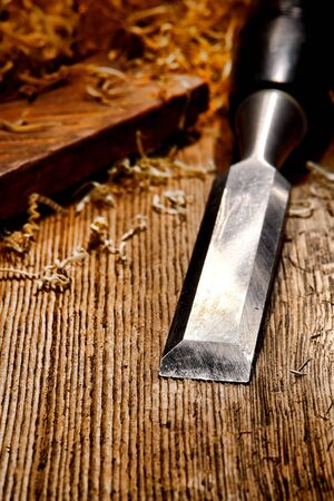 Used and worn carpenter wood chisel tool with loose shavings on old weathered distressed wooden board workbench in a vintage carpentry woodworking workshop  Banque d'images