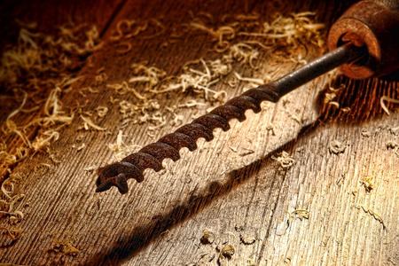 taladro: Rusty época de acero de gran broca de madera en la mano una herramienta de perforación manivela sobre grunge de edad degradado angustiada banco de madera, taller de bordo en un taller de carpintería para trabajar la madera antigua