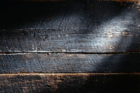 Old and distressed antique charcoal smoked burned board made of barn wood plank with rough weathered textured grain grunge background photo