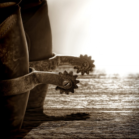 American West rodeo cowboy traditional leather boots with authentic western riding spurs on old weathered wood planks at sunset photo