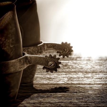 botas vaqueras: Oeste Americano botas de vaquero de rodeo tradicional de cuero con aut�nticos estribaciones occidentales de montar en edad resistido tablones de madera al atardecer Foto de archivo