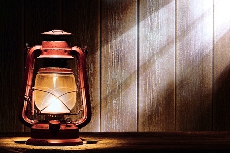 Old fashioned kerosene lantern style oil lamp burning with a soft glow light in an antique rustic country barn lit by diffused sunlight shining on a wood plank wall through a window 免版税图像
