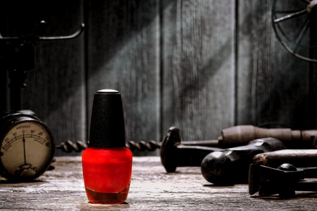 workbench: Generic bottle of bright fashion color red nail liquid polish cosmetics on a vintage weathered wood workbench with antique industrial tools in an old grunge mechanic workshop