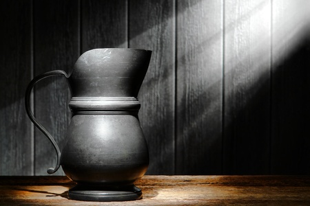pewter: Antique beverage serving pewter pitcher on an old wood shelf in an ancient historic home with soft diffused sunlight lighting an aged house wall through a window