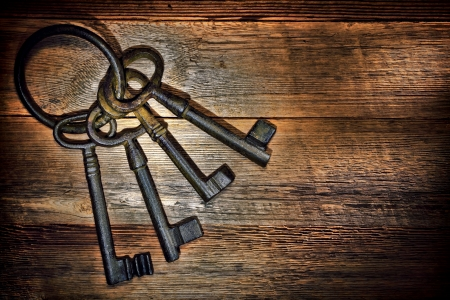 Antique and rusty medieval castle skeleton door keys with old corroded metal ring on antique weathered barn wood board planks photo