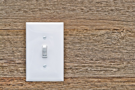 light switch: Traditional North American toggle white house electric light switch in ON position on aged old wood wall