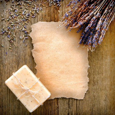Blank torn piece of recycled brown paper with empty copy space for text with dry lavender flowers bunch and natural aromatherapy bath soap bar on aged weathered wood board background Stock Photo - 12543359