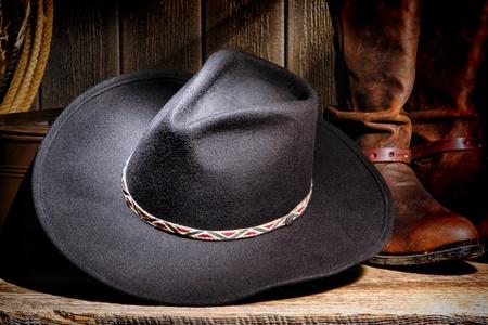 rodeo americano: American West Rodeo Cowboy sombrero de fieltro negro y auténticos de cuero marrón occidentales botas de montar de edad degradado granero rancho de piso de madera Foto de archivo