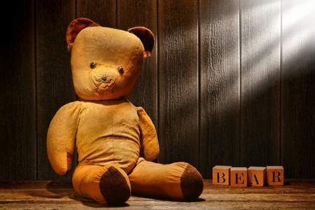 Old and used tan fabric vintage teddy bear stuffed animal toy with word spelled in antique alphabet blocks in an old house aged wood attic lit with filtered sunlight
