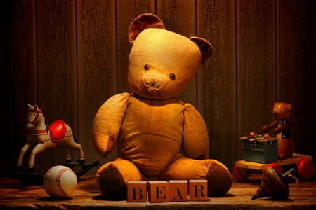 Old and used tan fabric vintage teddy bear stuffed animal with word spelled in antique alphabet blocks and retro play toys in an old historic house aged wood attic