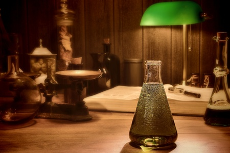 Antique science and chemistry research laboratory with an old conical glass lab Erlenmeyer flask filled with potion and vintage scientific instruments in retro faded colors