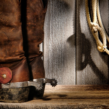 American West rodeo cowboy traditional leather boots with roping riding spurs and authentic Western lasso lariat on weathered barn wood background photo
