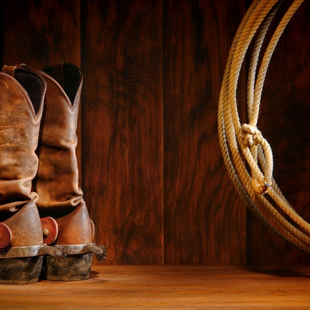 rodeo americano: Oeste Americano botas de vaquero de rodeo tradicional de cuero con espuelas de montar Roper y auténtico occidental lazo lazo sobre fondo de madera marrón granero