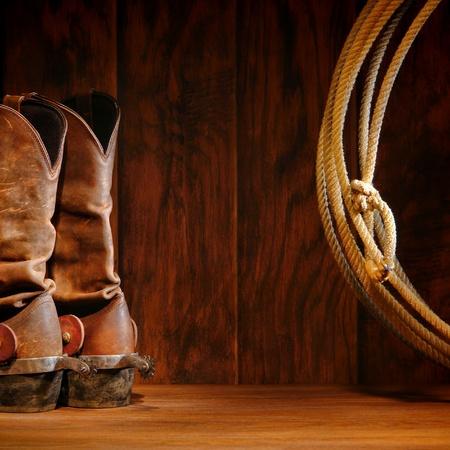 american rodeo: West americano rodeo stivali di pelle da cowboy tradizionali con Roper a cavallo speroni e autentico occidentale lasso lariat su sfondo marrone legno fienile