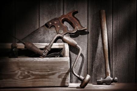carpintero: Viejo y antiguo carpintero y utiliza las herramientas de manitas con taladro y sierra de corte transversal y el martillo en una caja de herramientas de madera r�stica de edad en un taller de carpinter�a de �poca