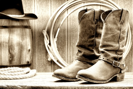 rodeo americano: American West Rodeo cowboy de cuero tradicional de trabajo ganadero botas Roper con aut�nticos estribaciones occidentales de montar en frente de un granero rancho de madera de la vendimia con lazo lazo y barril de madera vieja grunge sepia nostalgia Foto de archivo
