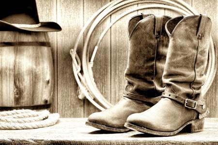 american rodeo: West americano rodeo cowboy in pelle lavorazione tradizionale rancher stivali Roper con autentici speroni occidentali a cavallo di fronte a un granaio d'epoca in legno ranch con lariat lazo e vecchia botte di legno in grunge nostalgico seppia