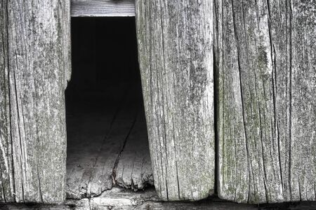 Old and weathered grey barn wall with empty hole from broken and missing barnwood board showing aged floor on an historic country farm house Stock Photo - 12837889