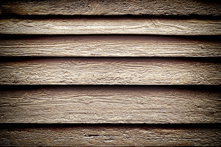distressed: Old weathered and distressed barn wood clapboard siding with aged irregular wooden planks on a historic home building wall as a grunge background in nostalgic sepia Stock Photo