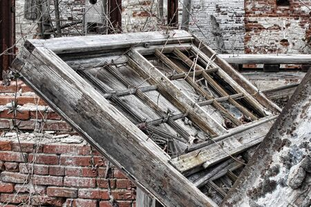 Old antique wood frame sash window fallen and broken in an abandoned and destroyed historic brick building after a minor earthquake  Stock Photo - 12837890