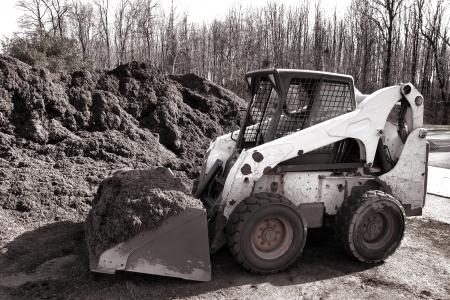 paillis: Compact d�rapage hydraulique orienter la machine les travaux au chargeur avec godet pelle cour charg�e et la cabine grille de s�curit� de creuser un tas de paillis organique pour un projet d'am�nagement paysager