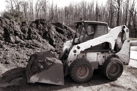 Compact hydraulic skid steer loader yard work machine with loaded excavator scoop and safety mesh cab digging a pile of organic mulch for a landscaping project  Stock Photo