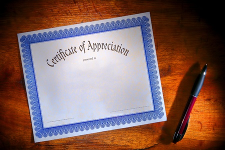 acknowledgement: Certificate of appreciation reward blank paper document ready to fill out with text and ballpoint ink pen for signature on a wood desk Stock Photo