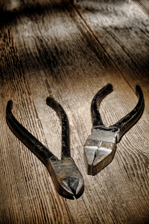 Vintage used and rusty pliers pairs tools on antique grunge weathered wood board workbench in an old carpentry shop Stock Photo - 12942096