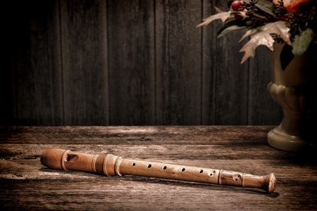 woodwind instrument: Old wooden recorder flute woodwind musical instrument with traditional classic baroque fingering holes on antique wood board table in a vintage historic home in aged olde master still life paint style