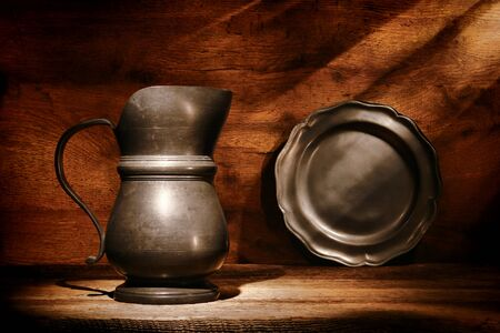 pewter: Antique colonial pewter serving pitcher and ancient metal plate on an old distressed wood shelf in a historic home