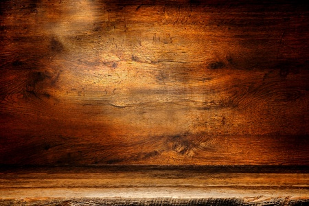 Old and distressed weathered wood plank surface in front of an antique rough sawn wooden board grunge background  photo