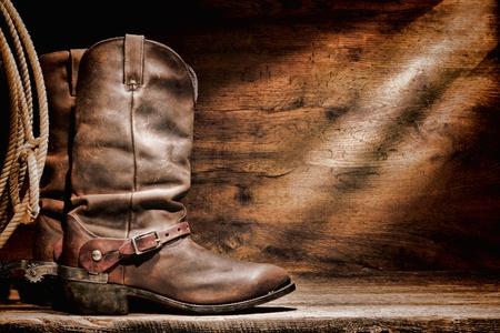 botas vaqueras: American West Rodeo cowboy de cuero tradicional, botas de trabajo Roper con aut�nticos estribaciones occidentales de montar y lazar lazo lazo en un granero viejo rancho vendimia piso de madera