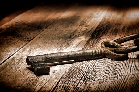 lock and key: Antique medieval skeleton door lock key on old and weathered wood planks