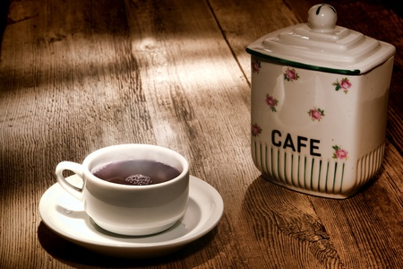 Cup of steamy hot black coffee with warm steam cloud in a white mug with vintage cafe ceramic jar on an old wood coffee shop counter table