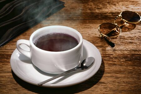 Cup of steamy hot black coffee with warm steam cloud in a white mug with traveler sunglasses and check bill folder on an old wood coffee shop or restaurant counter table photo