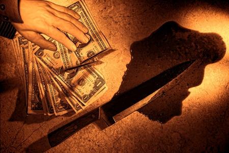 uccidere: Gruesome scena del crimine legale di un omicidio violento con la mano ha ucciso l'uomo morto in possesso di un pila di banconote da un dollaro vicino ad una sanguinosa un'arma coltello chef in una pozza di sangue sul pavimento come prova in un'indagine penale grunge ruvido seppia