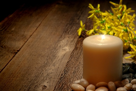 memorial candle: Spiritual meditation and reflection pillar candle burning with a bright sparkling flame and blooming yellow forsythia flowers on old weathered wood planks for a commemorative remembrance ceremony memorial Stock Photo